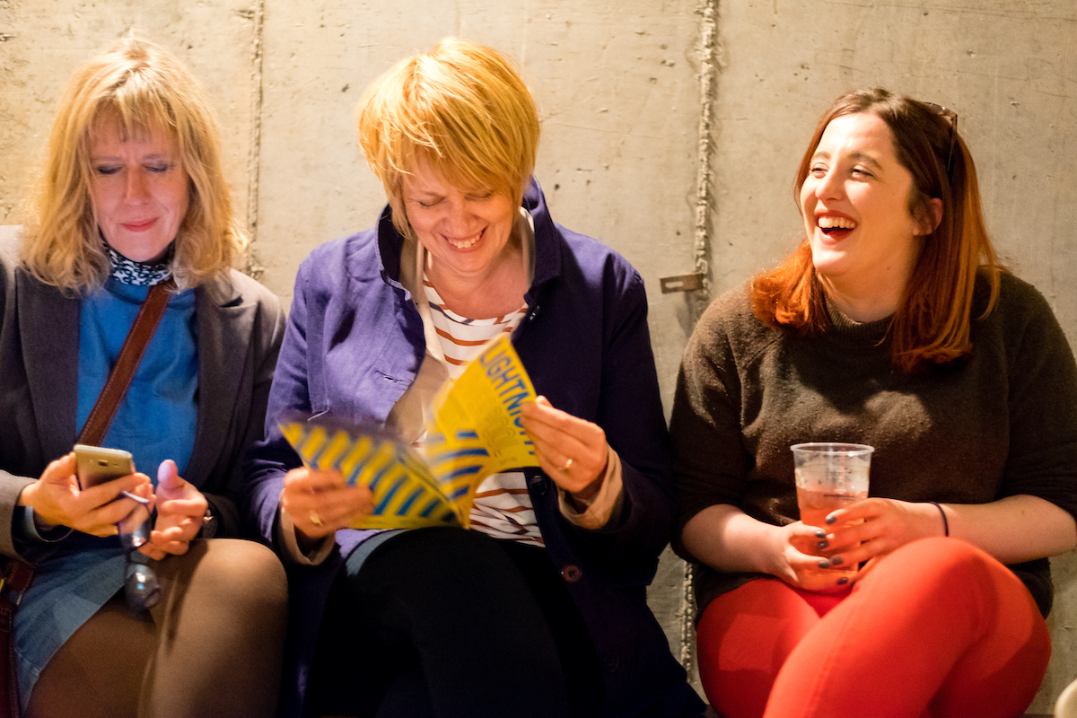Three seated women laughing and reading a Light Night brochure.