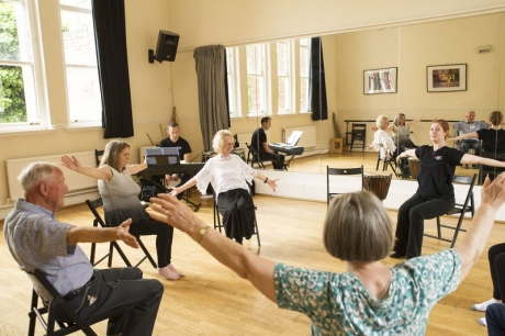 A group of older people sit in a circle of chairs, their arms in the air, taking part in a Dance for Parkinson's class.